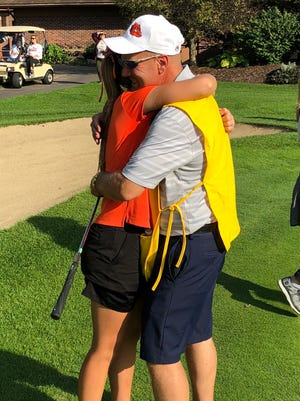 Brighton's Gracie Schueneman hugs her father after he caddied her final hole on senior day against Novi.