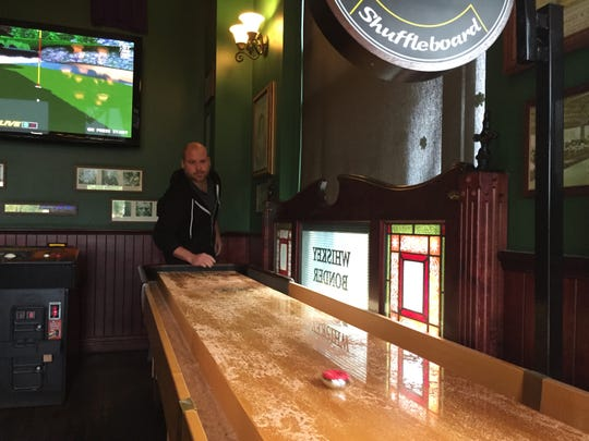 Jameson's Irish Pub and Grill General Manager Drew Hagedon demonstrates the pub's shuffleboard table at its former Green Oak Township location, Friday, Oct. 4, 2018. The pub is in the process of moving to downtown Brighton. Joe Kool's Sports Bar and Grill plans to open its second location in the space later this year.