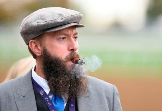 A man wears a gray cap and suit during day two of the 2015 Breeders' Cup World Championships at Keeneland Race Track.