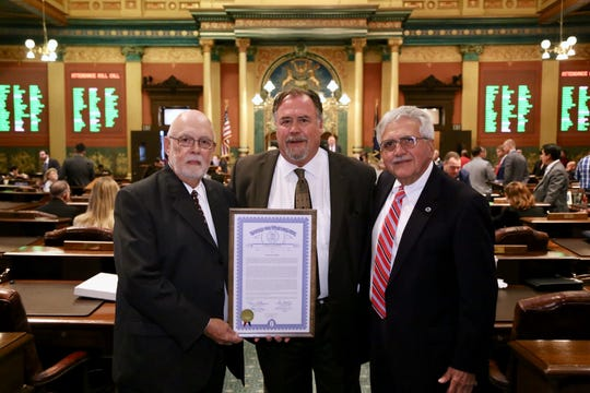 Duane Garver, Rep. Tom Cochran, D-Mason, and the Rev. Mike Bongart pose for a photograph after Cochran read a tribute to Garver on Oct. 4, 2018. Garver saved Bongart's life Oct. 4, 1968.