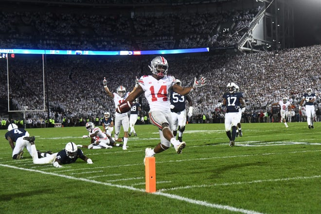 Ohio State receivers Terry McLaurin and Austin Mack, in the background, throw blocks to spring high-stepping K.J. Hill on he decisive game-winning TD pass against Penn State.