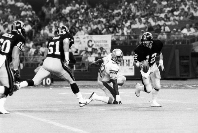 Houston Gamblers quarterback Jim Kelly scrambles away from the rush by Memphis Showboats defensive end Reggie White in the first quarter of the USFL game on Monday, June 25, 1984 in the Astrodome, Houston. Kelly found receiver Clarence Verdin for a 27-yard gain downfield.