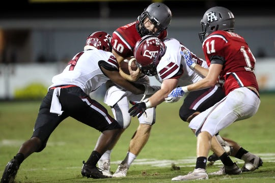 Fayette Academy's Rube scott Rhea is sacked by Davidson Academy's Mikyan Duncan, left, and Bryce Rawls during their game in Somerville on Thursday, Oct. 4, 2018.