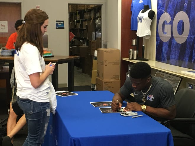 Former Memphis wide receiver Anthony Miller, now with the Chicago Bears, signs an autograph during a signing at the University of Memphis bookstore Friday