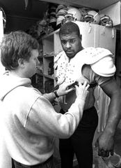 January 30, 1984 - Memphis Showboats equipment manager Wayne Reed fits Reggie White with shoulder pads as White checks in for training camp with the USFL team.