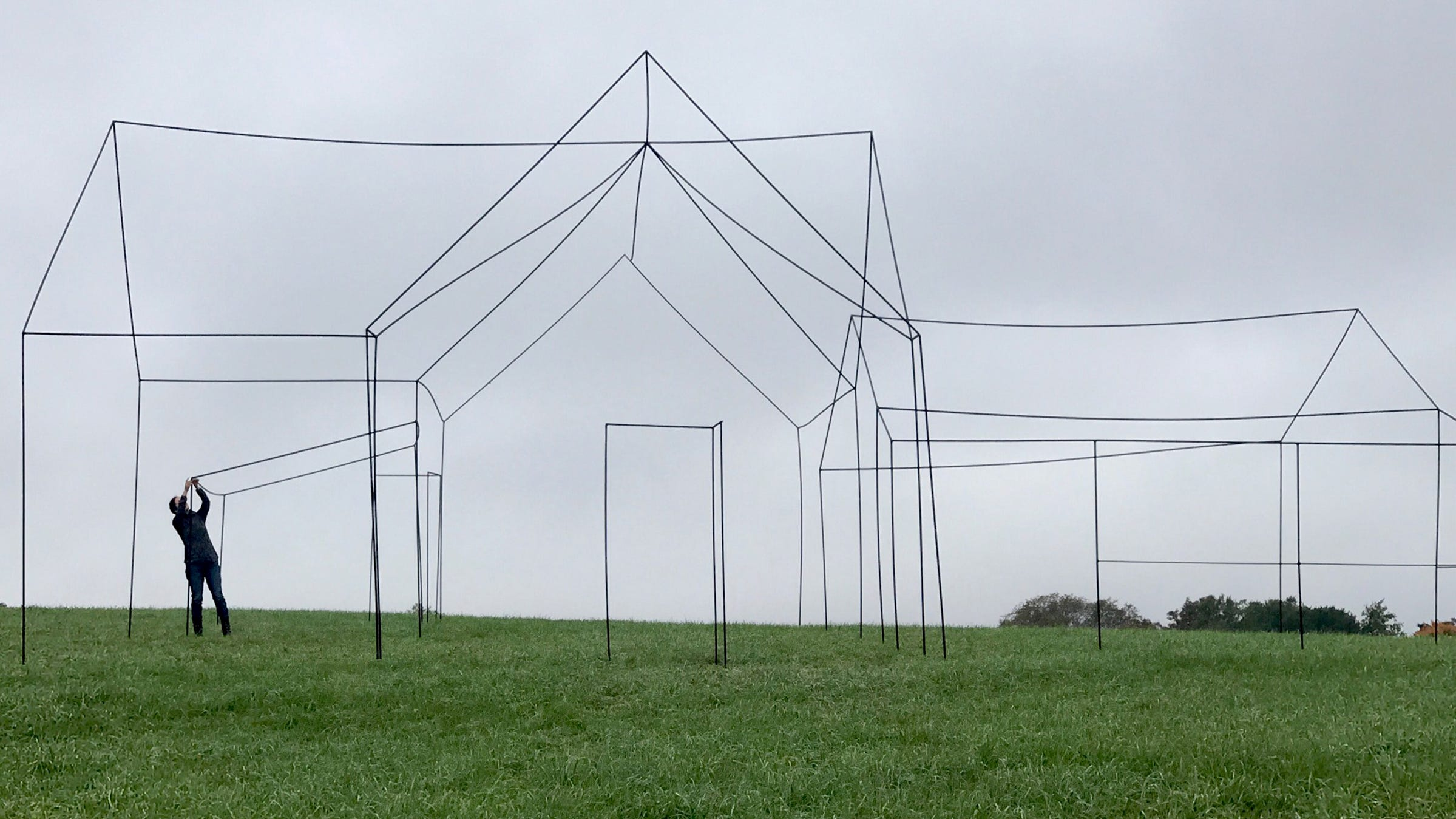 """Sarah FitzSimon's artwork looks like a pencil drawing against the sky. Visitors can walk through the full-scale, three-dimensional """"sketch"""" of a farmhouse in the Driftless Area of Wisconsin. It is part of Farm Art DTour, an open-air art exhibit along 50 miles of winding country roads in Sauk County running through Oct. 14."""