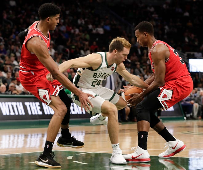 Milwaukee Bucks' Pat Connaughton loses the ball as he drives between Chicago Bulls' Chandler Hutchison and Wendell Carter Jr. during the second half of an NBA preseason basketball game Wednesday, Oct. 3, 2018, in Milwaukee. (AP Photo/Morry Gash) ORG XMIT: WIMG112
