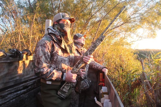 Dan Rammer (left) and Jack Grassmann, both of Neenah, watch the skies from a blind on opening morning of the Wisconsin duck hunting season.