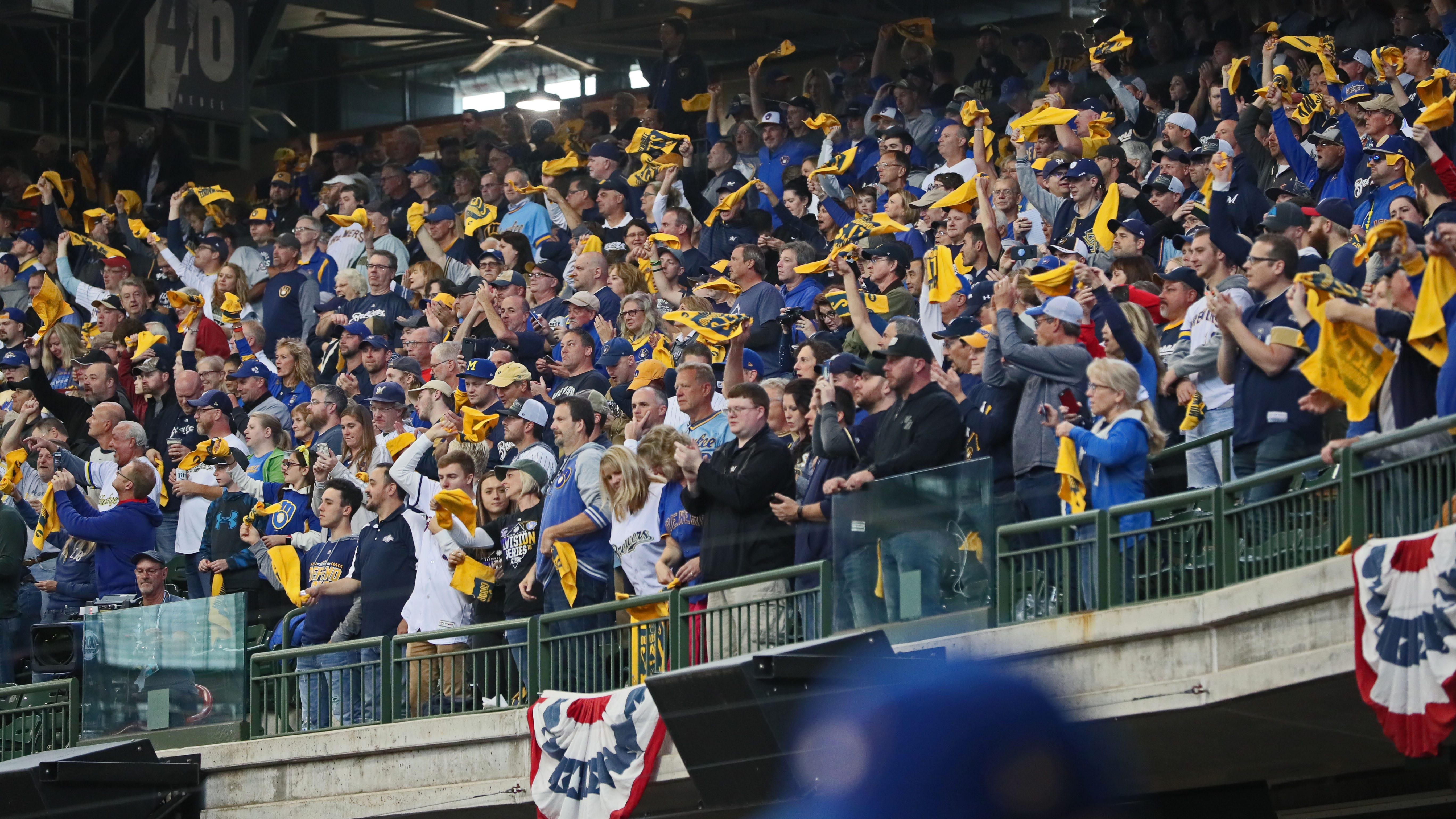 Fans wave their souvenir towels to cheer on the Brewers.