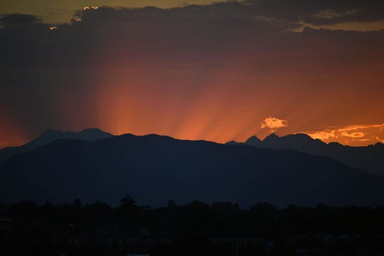 The view behind Coors Field as the sun sets behind the Rocky Mountains in the fifth inning between the Seattle Mariners against the Colorado Rockies on July 11, 2018