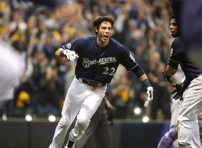 An exultant Christian Yelich heads to join his teammates, who had gone out to celebrate with Mike Moustakas in right field after he provided the game-winning hit in Game 1 against the Rockies on Thursday night at Miller Park.