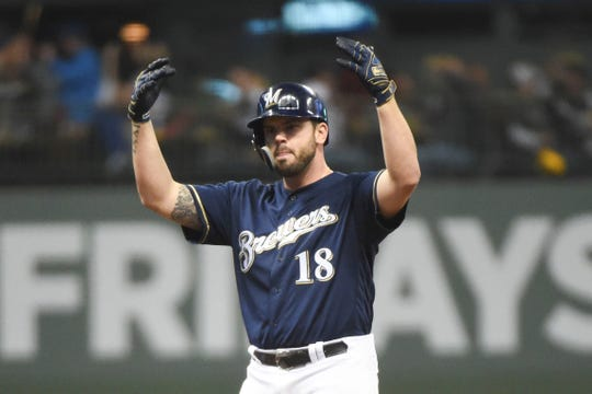 Mike Moustakas gestures toward the Brewers' dugout after leading off the bottom of the third inning with a double during Game 2 of the NL Division Series against the Rockies on Friday at Miller Park.