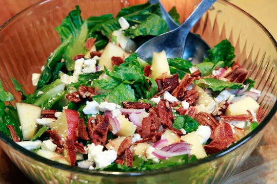 Chopped autumn salad with apple  and spears and cider dressing also features bacon and pecans.