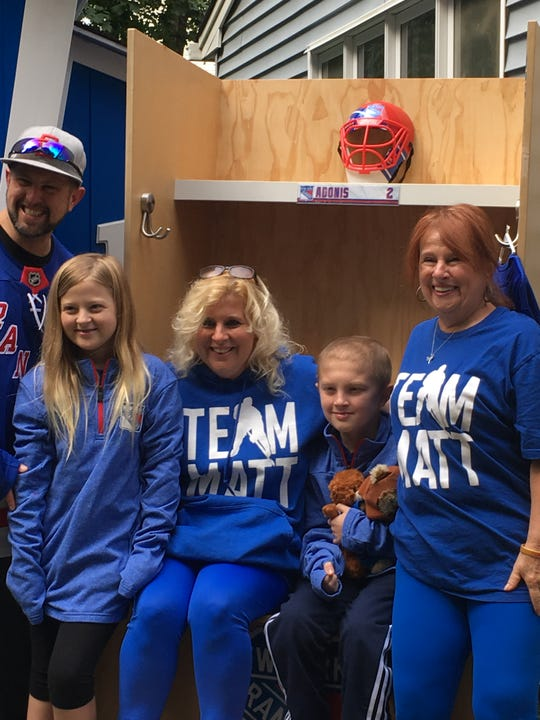 Matt Adonis (center) and his twin sister Mady, their parents Mark and Alyssa Adonis, and grandmother Elise Ryan, pose in the Rangers-themed locker set up in their Roxbury yard, a gift from Make-a-Wish NJ and the Garden of Dreams Foundation.