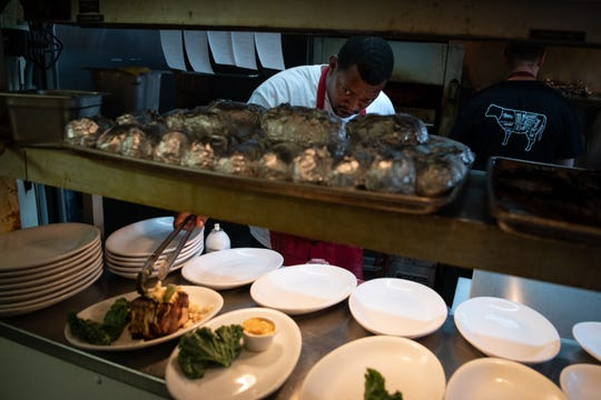 Cook Antowan Malone puts the final touches on a steak in the kitchen at Jimmy Kelly's Steakhouse in Nashville, Tenn., Thursday, Oct. 4, 2018.