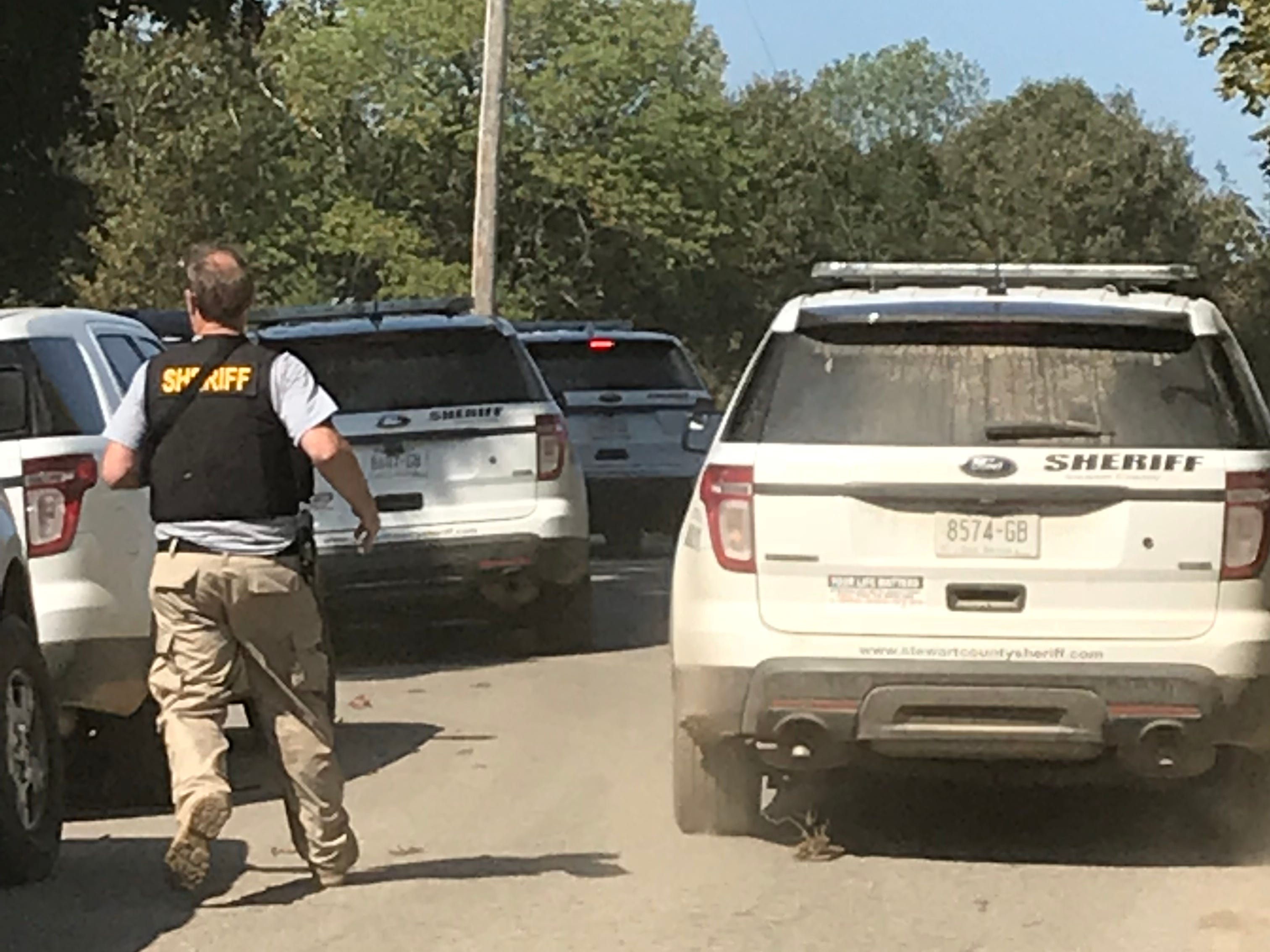 Sheriff's deputies and police officers depart after Kirby Wallace was arrested Friday morning in Stewart County.