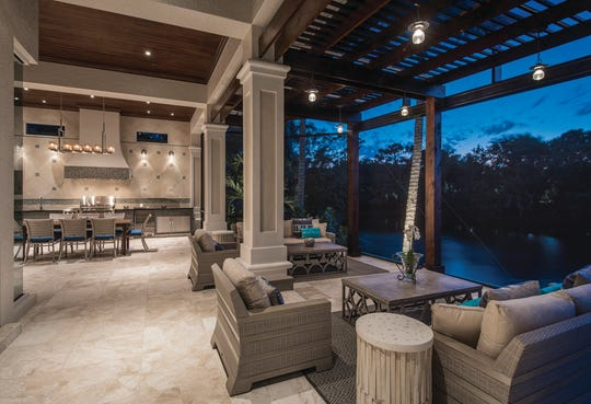 After: Harwick Homes remodeled the outdoor living space by creating an expanded patio featuring an all-weather outdoor kitchen built adjacent to a wooden pergola that offers shade and additional space