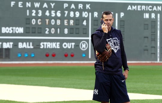 New York Yankees manager Aaron Boone talks on his phone at Fenway Park, Thursday, Oct. 4, 2018, in Boston. The Yankees are scheduled to face the Boston Red Sox in Game 1 of the AL Division Series on Friday.