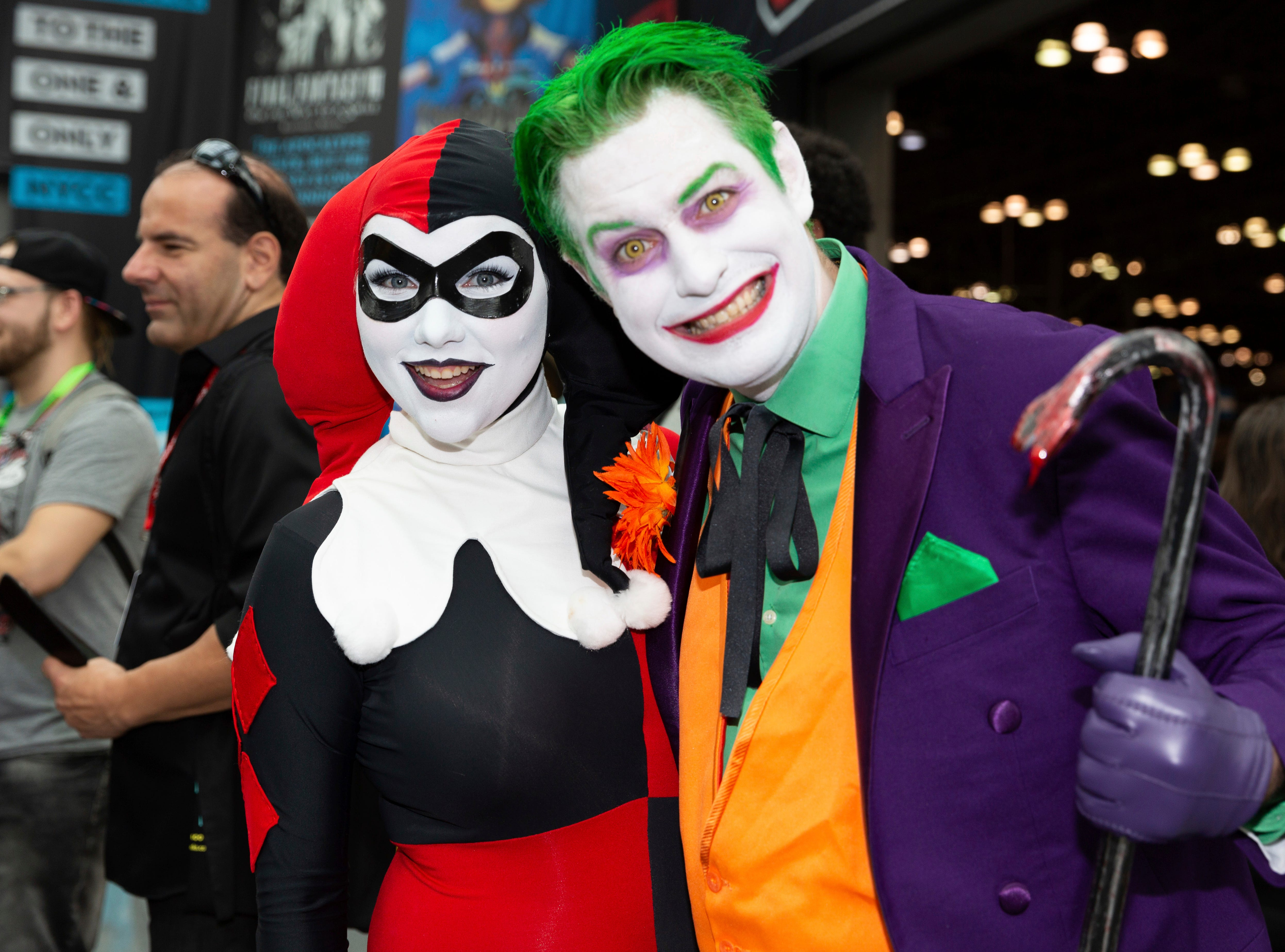 Attendees dressed as Harley Quinn, left, and The Joker pose for a photo during the first day of New York Comic Con, Thursday, Oct. 4, 2018. (AP Photo/Steve Luciano)