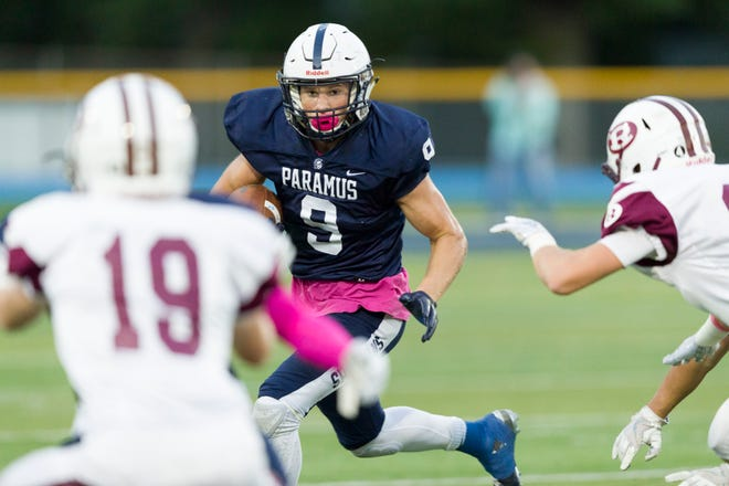 Paramus ballcarrier Kyle Jacob (9) stares down Ridgewood defenders Kevin Seitter (19) and John Kearney in the first quarter of Friday night's high school football showdown in Paramus.