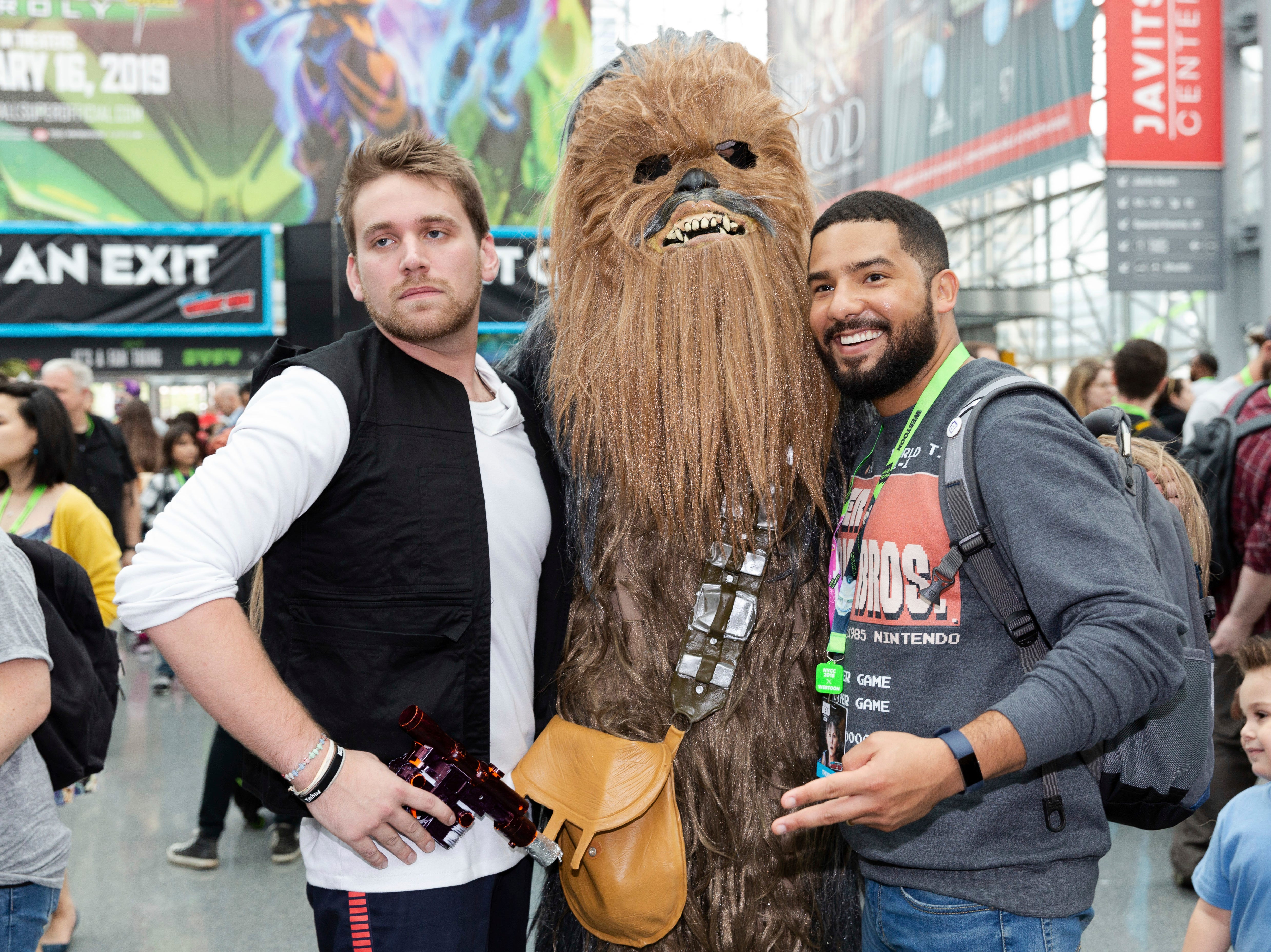 Attendees dressed as Han Solo, left, and Chewbacca, center, from Star Wars pose for a photo with a fan during the first day of New York Comic Con, Thursday, Oct. 4, 2018. (AP Photo/Steve Luciano)