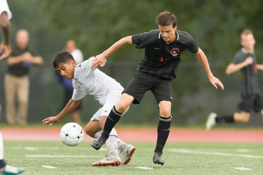 Jose Intriago of Lyndhurst (left) grapples for the ball with Glen Rock's Connor Daly (13) in the first round of the Bergen County High School Boys Soccer Tournament in Glen Rock. Glen Rock rolled to a 6-0 victory.