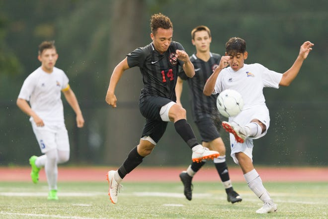 Glen Rock's Eddie Felipe (14) battles Lyndhurst's Jose Intriago for the ball in the first round of the Bergen County High School Boys Soccer Tournament in Glen Rock. Glen Rock rolled to a 6-0 victory.
