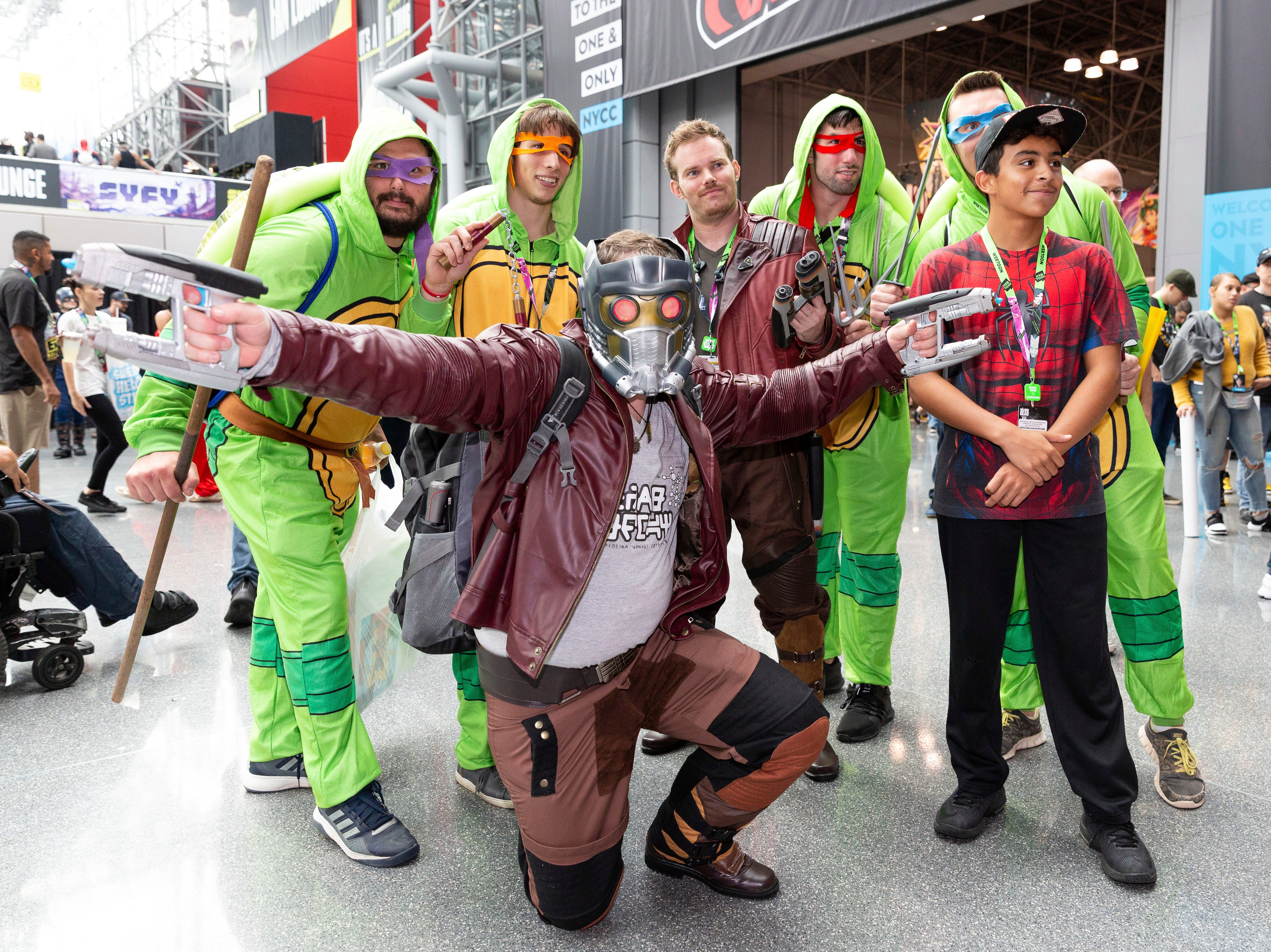 Attendees dressed in costume pose for a photo with a fan during the first day of New York Comic Con, Thursday, Oct. 4, 2018. (AP Photo/Steve Luciano)