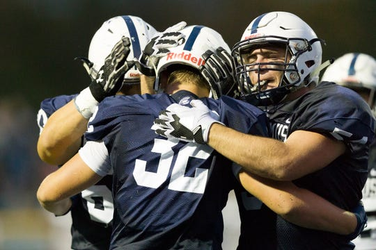 Paramus runner Brandon Dell Colle (32) gets congratulated by teammates after scoring against Ridgewood in Friday night's high school football showdown in Paramus.