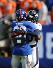 115725 Bergen; East Rutherford, NJ MetLife Stadium 9/15/2013 Denver Broncos Mike Adams, of Paterson, hugs New York Giants Victor Cruz, also from Paterson, prior to Sunday's Broncos win.
