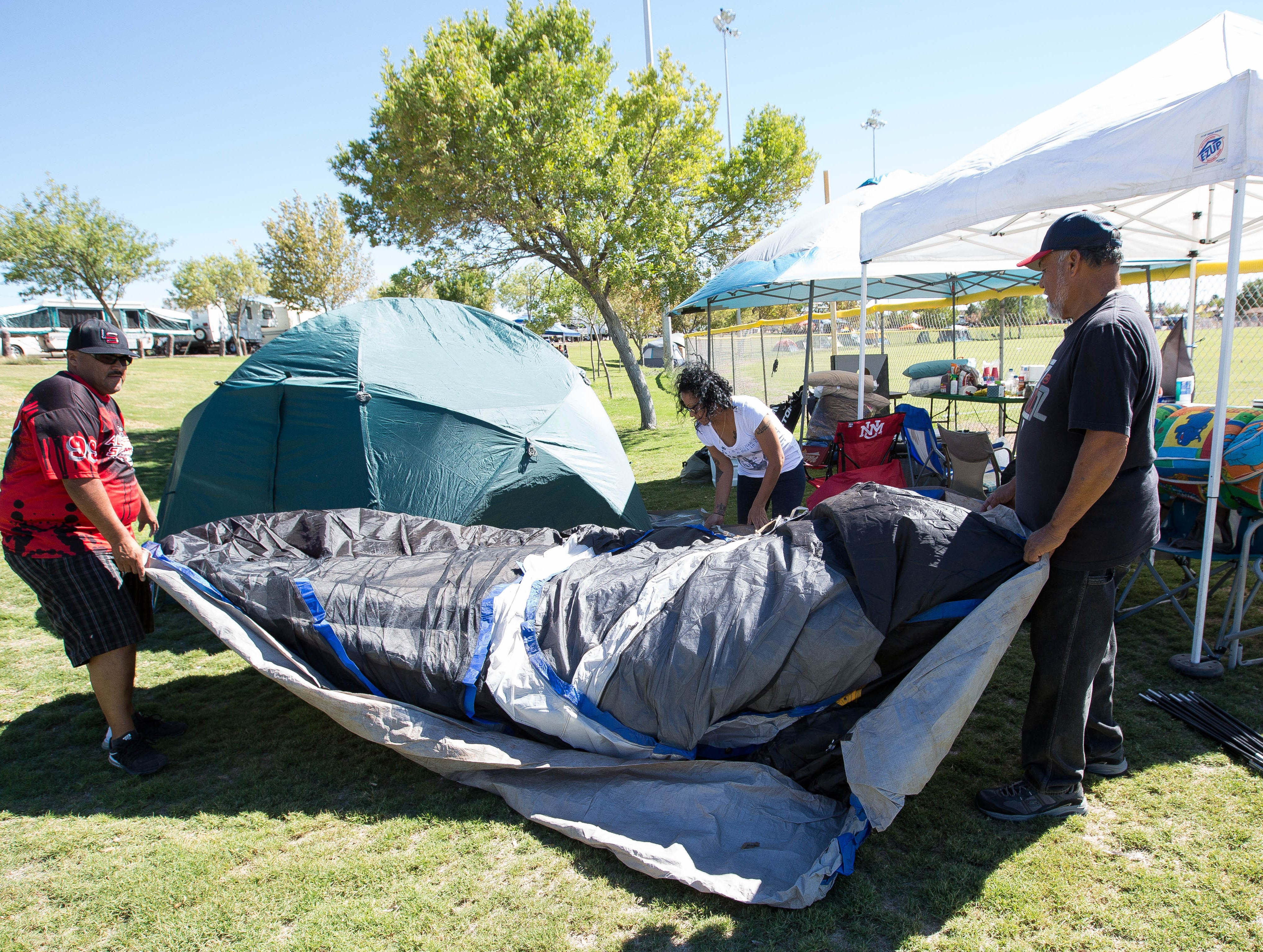 Ivan Soto, left, Maria Carrillo, center, and Chelo Soto, right, from Albuquerque, set up tents for their softball team La Raza Friday Oct. 5, 2018 at Maag Park. More than 7,000 softball players are expected for this weekend's round-the-clock tournament.