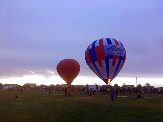 In this Oct. 6, 2017 file photo hot air balloons from the upcoming Albuquerque International Balloon Fiesta inflate for students at Enchanted Hills Elementary School in Rio Rancho, N.M. The 47th Albuquerque International Balloon Fiesta is set to start Saturday, Oct. 6, 2018, and will feature nearly 600 hot air balloons. The event is expected to draw around million visitors to central New Mexico but comes as Albuquerque continues to struggle with crime.