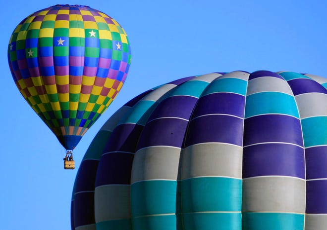 In this Oct. 10, 2017, file photo, hot air balloons participating in the Albuquerque International Balloon Fiesta float over Albuquerque, N.M. The 47th Albuquerque International Balloon Fiesta is set to start Saturday, Oct. 6, 2018, and will feature nearly 600 hot air balloons.