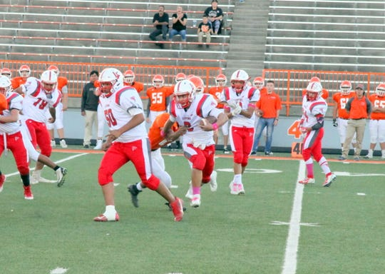 Loving quarterback Kevin Gut-omen tries to break a tackle against the Artesia JV squad in the first half of Thursday's game. Gut-omen finished the game with three rushing touchdowns.