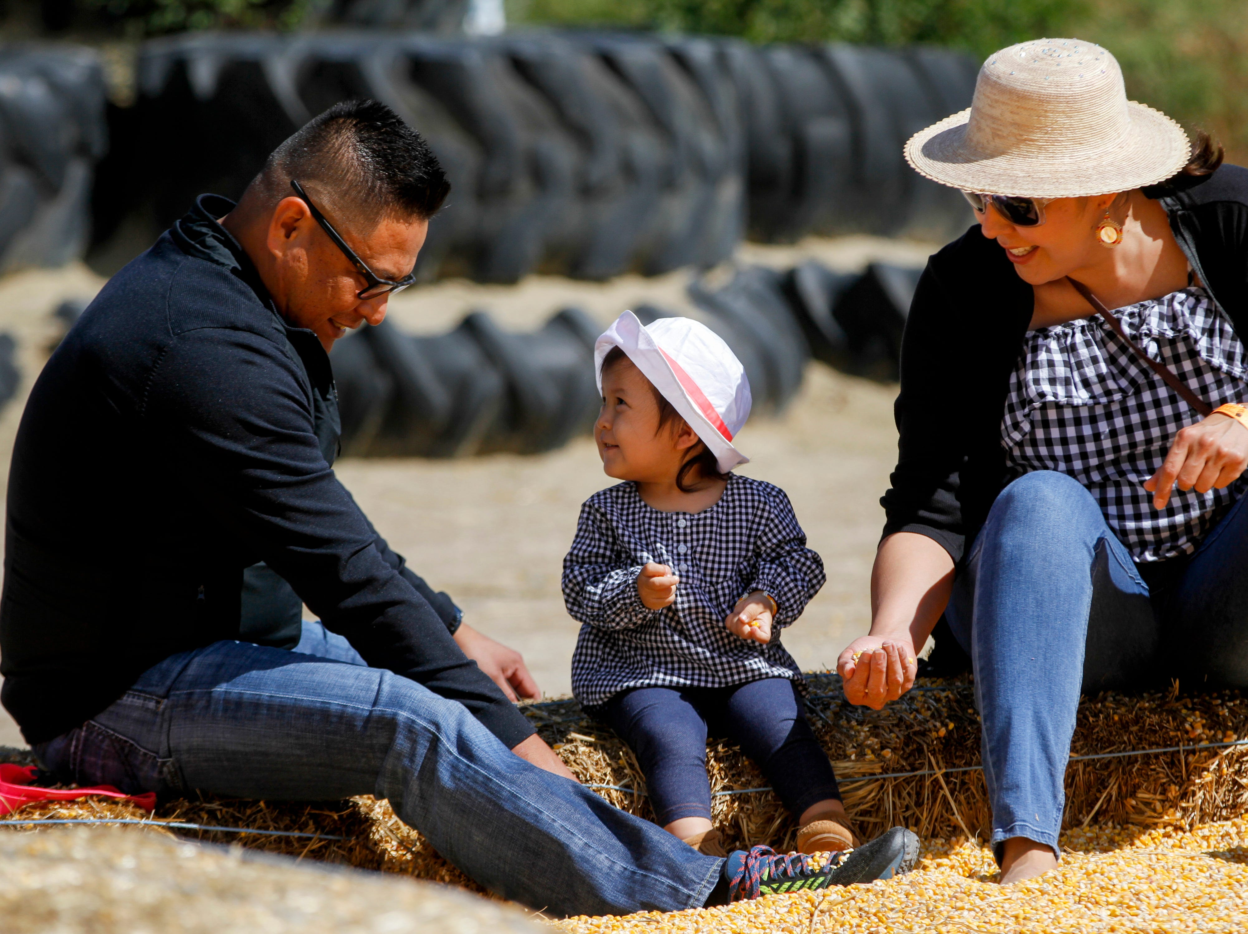 Tansa Bitsie, center, plays with her parents Thurman Bitsie, left, and Lori Todacheene, all for  Friday, Oct. 5, 2018 inside a corn pit at Sutherland Farms in Aztec.