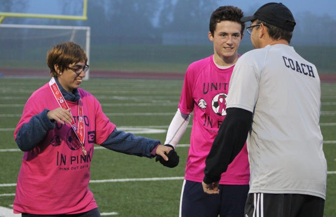 Gold medal winner Chelsey Ramsay is accompanied by a South Lyon player during the recent Pink Out game at South Lyon High School.