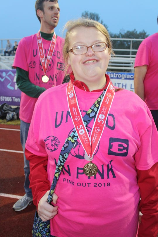 South Lyon Special Stars player Nicole Sawle proudly displays her gold medal at South Lyon High School during the recent Pink Out game against South Lyon East.