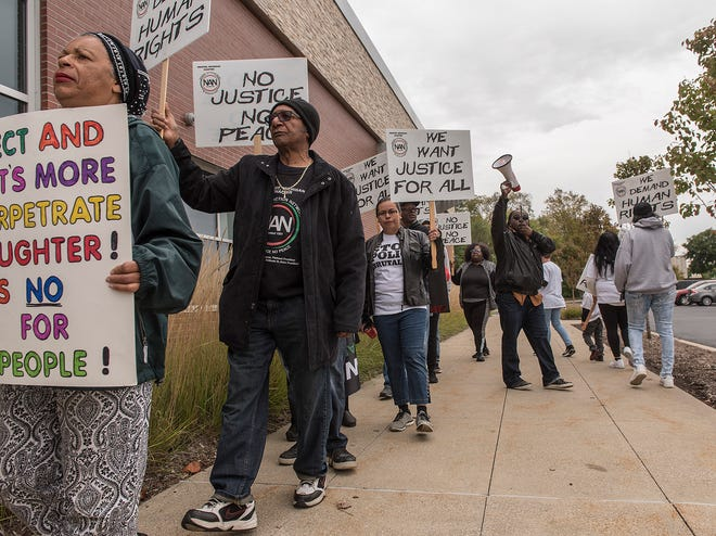 Will Miller, center, president of the Inkster/Western Wayne County chapter of the National Action Network, leads marchers in a chant outside Westland City Hall on Friday.