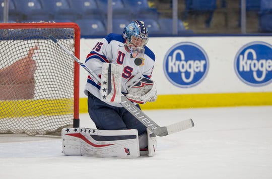 Tracking the puck into his USA crest during a 2017-18 game is goalie Spencer Knight.