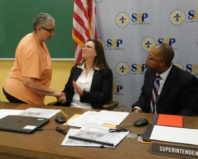 School employee JoElla Leblanc shakes hands with board president Candace Gerace at the end of Thursday's meeting. At right is superintendent Patrick Jenkins.