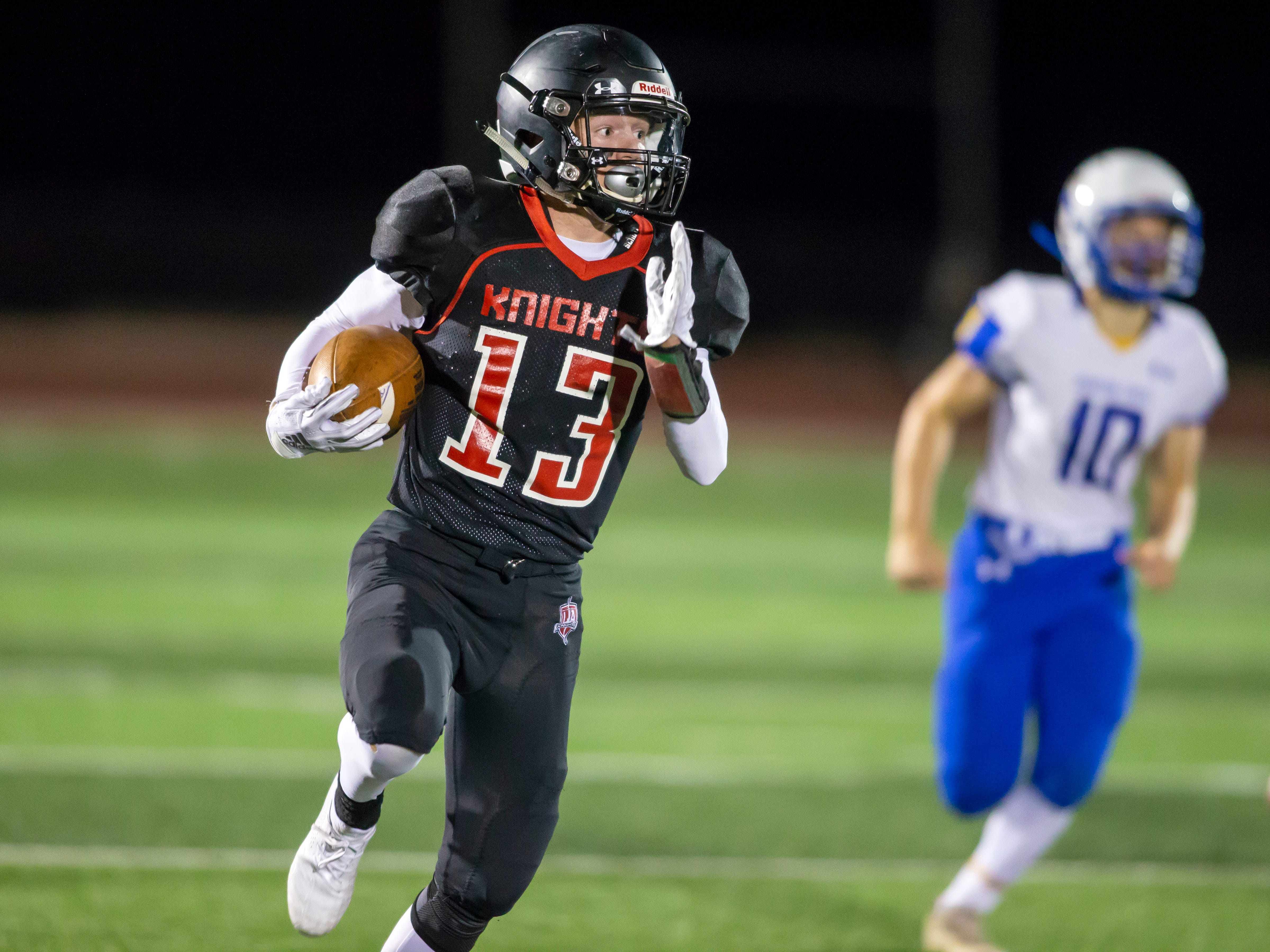 Lourdes Academy's Colton Clark finds running room on the Knights' first offensive play against Johnson Creek on J.J. Keller Field at Titan Stadium Thursday, October 4, 2018.