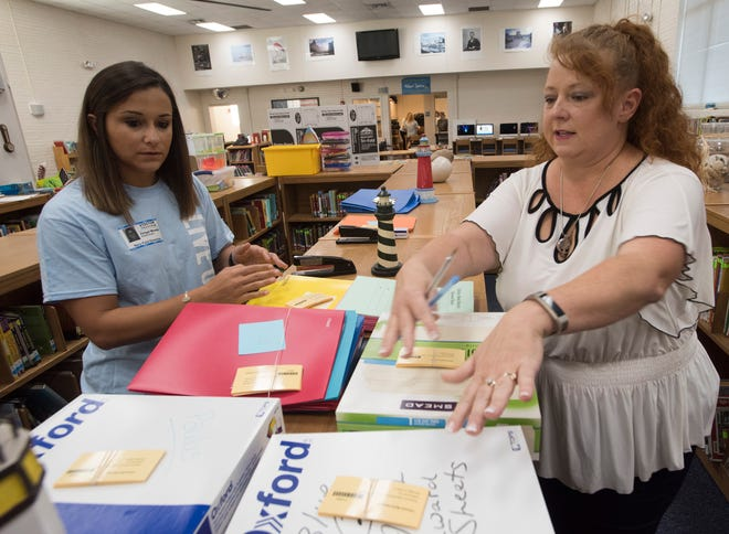Abigail Miranda, a volunteer with United Way of Escambia County's Day of Caring, gets instructions Friday from Navy Point Elementary School librarian Tiffany Rose on how to help out at the school.