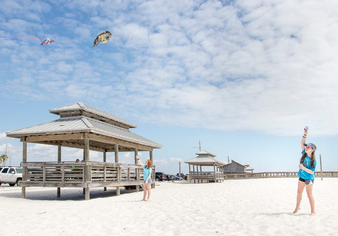 Jacycilynn Conger, 16, left, and her sister Allison, of Enterprise, Alabama, fly kites in the sandy area next to the parking lot at Navarre Beach on Friday, October 5, 2018.  Santa Rosa County may spend a portion of the $3 million bed tax revenue overage on improving the facilities in the area near the fishing pier.