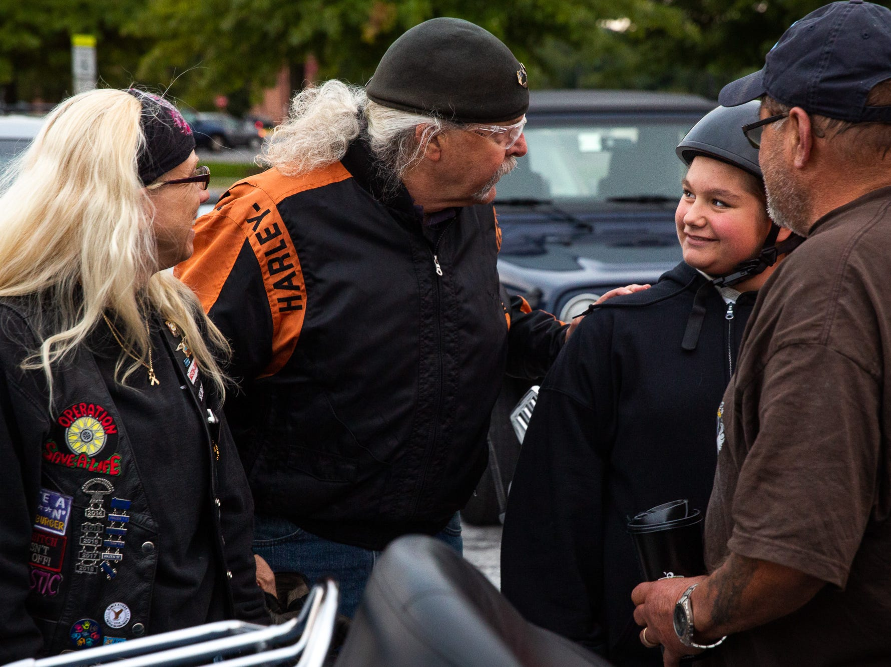 Aireana Mummerth, a 6th grader, is embraced by bikers after arriving to school at Emory H. Markle Intermediate escorted by dozens of members of the Alliance of Bikers Aimed Toward Education biker group, Friday, Oct. 5, 2018, in Penn Township.