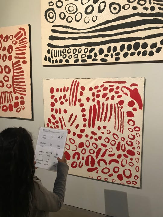 One of Candace Green's sixth-grade students from Sevilla West Elementary School in Phoenix studies a piece of art at Scottsdale Museum of Contemporary Art on a field trip paid for by the nonprofit Act One.