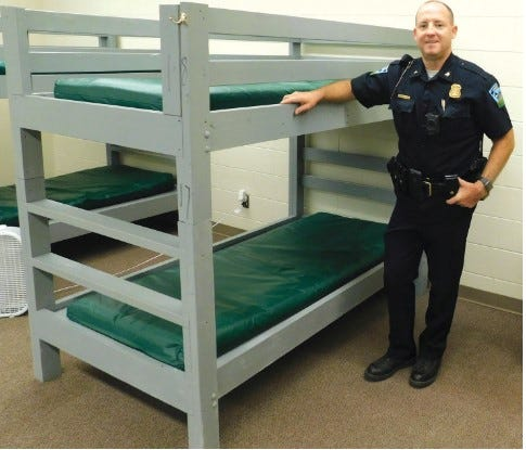 Sandusky Police Chief Brett Lester with one of the beds at the Sanilac Rescue Mission