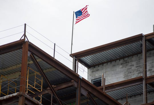 A flag was raised at the top of the Bluewater View condos in Port Huron after the frame of the first tower reached its final height of 136 feet.