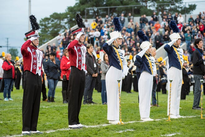 Drum majors from the Port Huron and Port Huron Northern High School marching bands stand at attention as their bands play the National Anthem Friday, Oct. 5, 2018 before the Crosstown Showdown at Memorial Stadium.