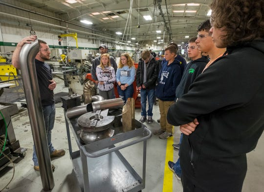 PauMac Tubing lead bender Andrew Weingartz, left, shows a piece of bent tubing to a group of Marysville High School sophomores during a tour on Manufacturing Day Friday, Oct. 5, 2018 at the PauMac plant in Marysville.