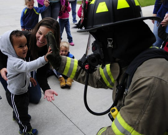 Sterling Rivers, 2, exchanges a high five with Kimball firefighter Cord Varty during a fire safety presentation on Friday, Oct. 5, 2018.
